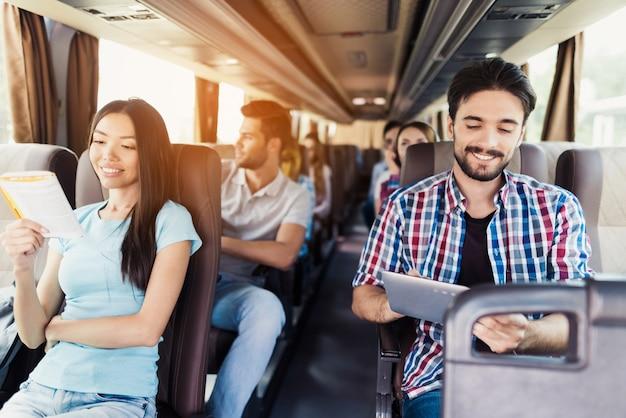 Entspannte junge passagiere im touristenreisebus. Premium Fotos