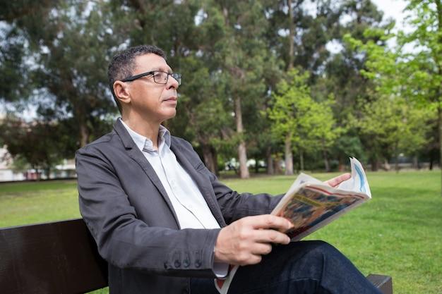 Entspannte mannlesezeitung und sitzen auf bank im park Kostenlose Fotos