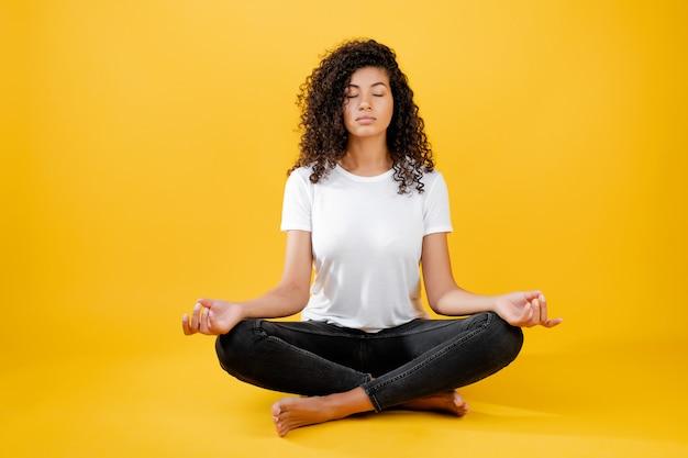 Entspannte schwarze frau, die in der yogahaltung getrennt über gelb meditiert Premium Fotos