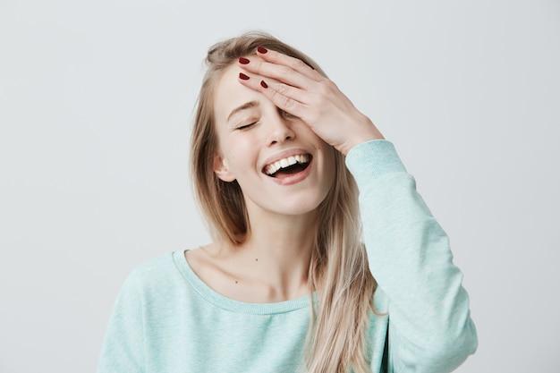 Entspannte sorglose frau mit blonden haaren, geschlossenen augen und breitem lächeln, freizeitkleidung, hand auf dem kopf haltend, die augen schließend, während sie von etwas angenehmem träumt. freude und emotionen Kostenlose Fotos