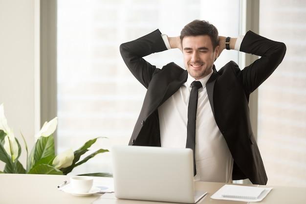 Entspannter angestellter, der das ergebnis der guten arbeit erledigt genießt Kostenlose Fotos