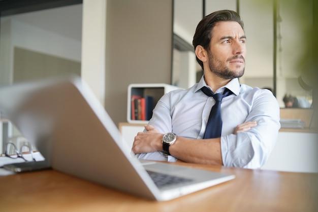Entspannter attraktiver geschäftsmann, der im modernen büro arbeitet Premium Fotos