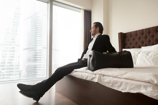 Entspannter geschäftsmann, der auf bett außer gepäcktasche sitzt. Kostenlose Fotos