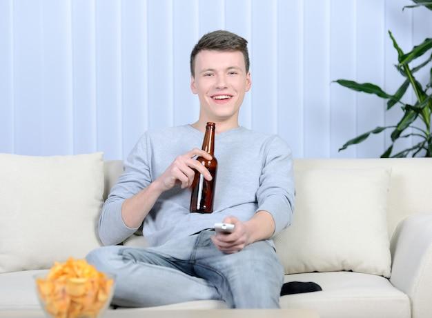 Entspannter junger mann, der fernsieht und bier trinkt. Premium Fotos