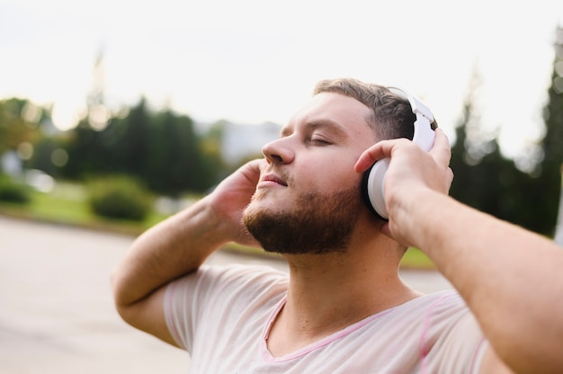 Entspannter mann, der kopfhörer mit seinen händen hält Kostenlose Fotos