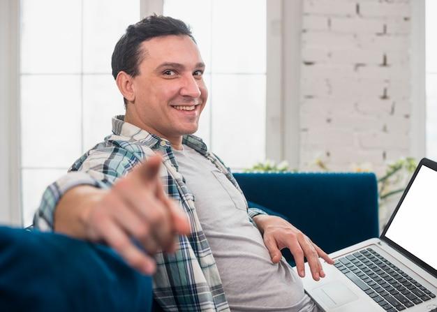 Entspannter mann, der zu hause laptop verwendet Kostenlose Fotos
