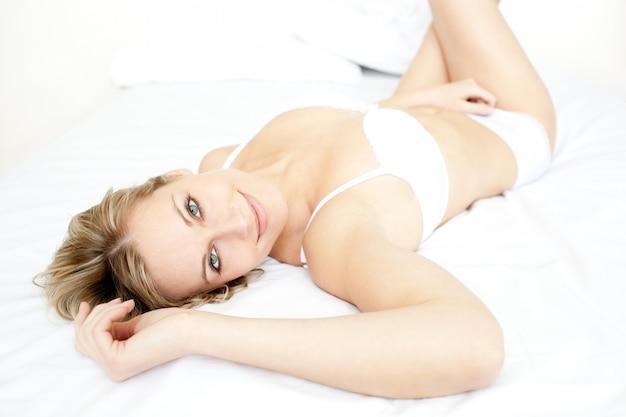 Entspanntes lügen der begeisterten frau auf ihrem bett liegend Premium Fotos