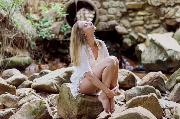 Entspanntes Mädchen sitzt auf einem Felsen im Freien Kostenlose Fotos