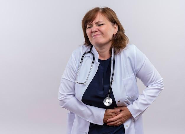 Enttäuschte ärztin mittleren alters, die medizinische robe und stethoskophände auf nieren trägt, die unter nierenschmerzen auf isolierter weißer wand mit kopienraum leiden Kostenlose Fotos