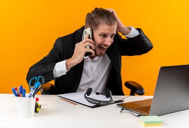 Enttäuschter gutaussehender geschäftsmann im anzug, der am laptop arbeitet, der auf handy spricht, verwirrt und unzufrieden am tisch in offise über orange hintergrund sitzt Kostenlose Fotos