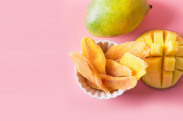 Entwässerte und getrocknete mangochips auf rosa abschluss oben Premium Fotos
