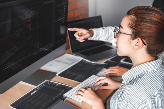 Entwickeln des programmiererteams, das computercodes liest entwicklung website-design Premium Fotos