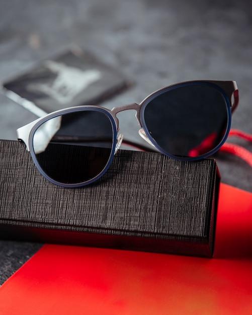 Entworfene sonnenbrille auf dem roten buch und der grauen oberfläche Kostenlose Fotos