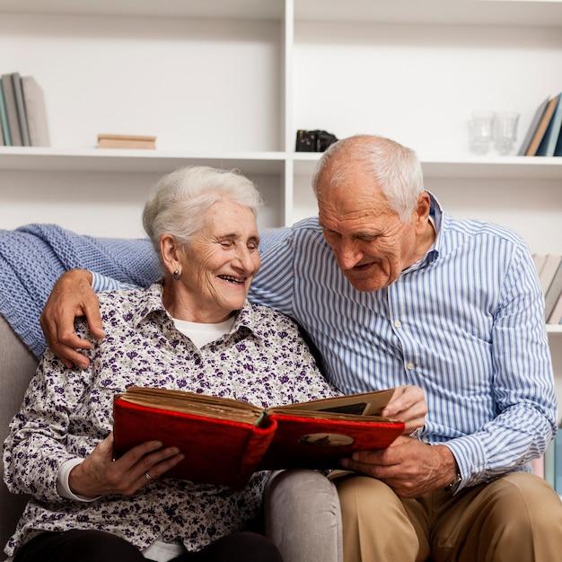 Entzückende ältere paare, die fotoalbum untersuchen Premium Fotos