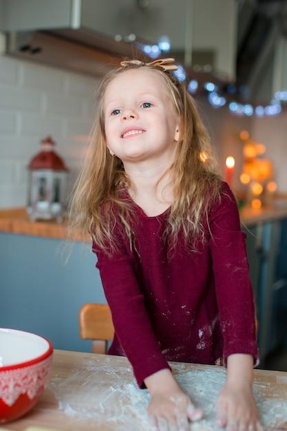 Entzückende backenweihnachtslebkuchenplätzchen des kleinen mädchens Premium Fotos