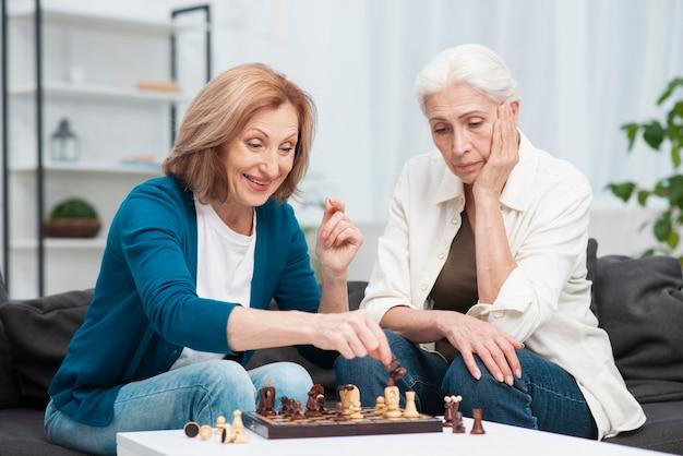 Entzückende frauen, die zusammen schach spielen Kostenlose Fotos