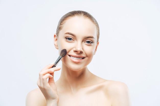 Entzückende junge brünette frau trägt kosmetische tongrundierung mit schönheitspinsel auf Premium Fotos
