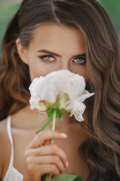 Entzückende junge frau hält weiße blume vor ihrem gesicht Kostenlose Fotos