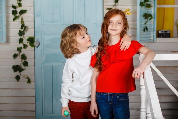 Entzückende kinder in farbigen kleidern, die urlaub genießen. lustige momente. frühlingsferienkonzept. junge und frau spielen. Premium Fotos
