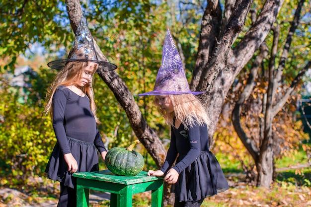 Entzückende kleine hexen haben spaß draußen an halloween. süßes oder saures. Premium Fotos