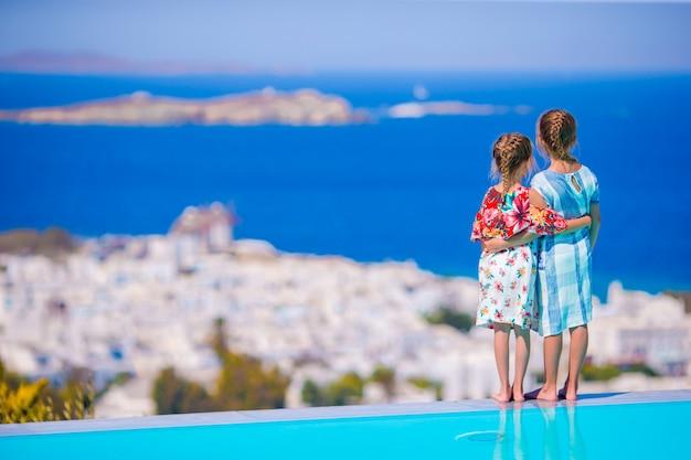 Entzückende kleine mädchen am rande des außenpools mit herrlichem blick auf berühmte sehenswürdigkeiten in griechenland Premium Fotos