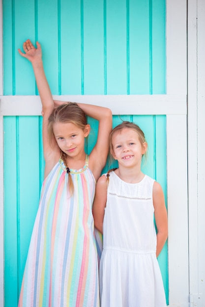Entzückende kleine mädchen auf traditionellem buntem karibischem haus des sommerferienhintergrundes Premium Fotos