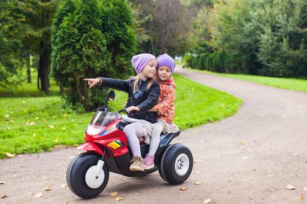 Entzückende kleine mädchen, die auf fahrrad des kindes im grünen park fahren Premium Fotos