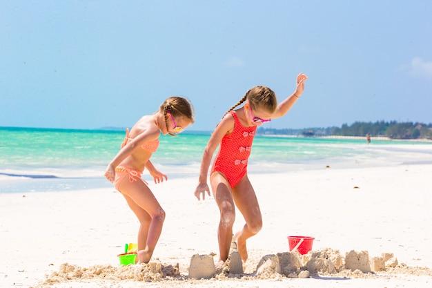 Entzückende kleine mädchen während der sommerferien. die kinder, die mit strand spielen, spielen auf dem weißen strand Premium Fotos