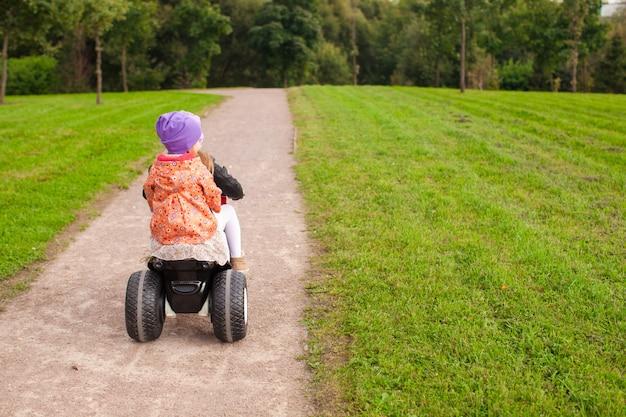 Entzückende kleine süße mädchen fahren draußen ein motorrad Premium Fotos