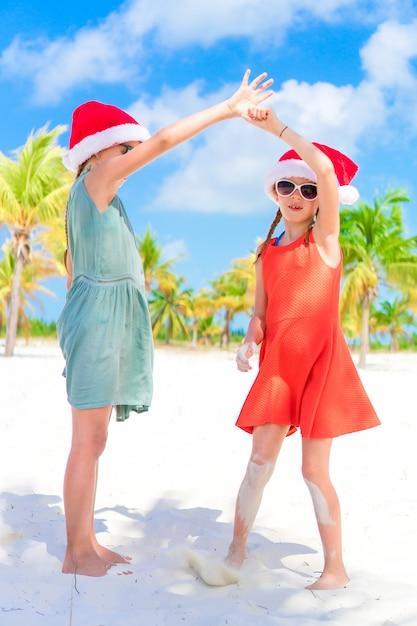 Entzückende kleinkinder in sankt-hut während der weihnachtsstrandferien. neues jahr am strand Premium Fotos