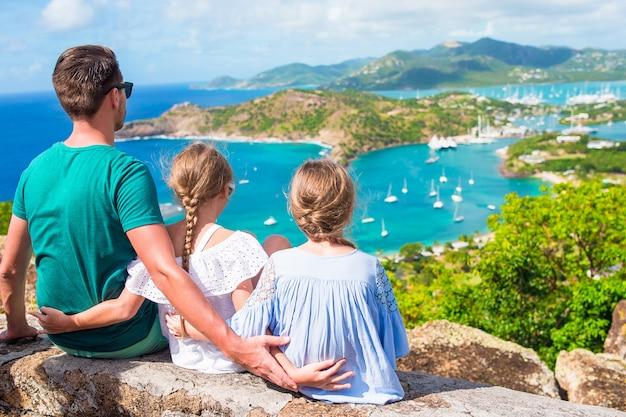 Entzückende kleinkinder und junger vater, welche die ansicht des malerischen englischen hafens in antigua im karibischen meer genießen Premium Fotos
