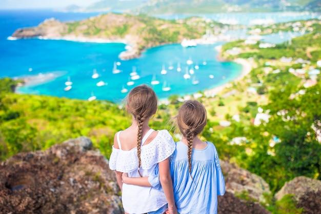 Entzückende kleinkinder, welche die ansicht des malerischen englischen hafens in antigua im karibischen meer genießen Premium Fotos