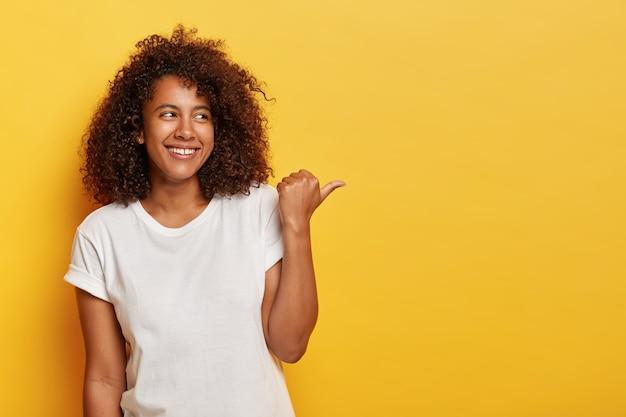 Entzückende studentin mit buschigem lockigem haar zeigt mit dem daumen nach rechts, fühlt sich glücklich und entspannt, trägt ein weißes freizeithemd, hat ein aufrichtiges lächeln im gesicht, isoliert auf gelber wand, zeigt etwas interessantes Kostenlose Fotos