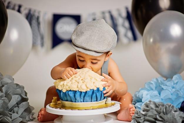 Entzückender glücklicher kleiner junge mit einem kuchen, um einen geburtstag zu feiern Premium Fotos