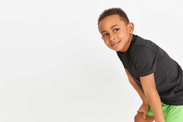 Entzückender kleiner junge im schwarzen t-shirt und in den grünen shorts, die während des cardio-trainings ruhen und hände über seinen knien halten Kostenlose Fotos