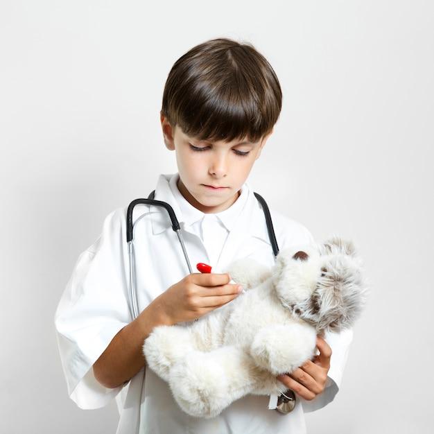 Entzückender netter junge, der einen teddybären hält Kostenlose Fotos