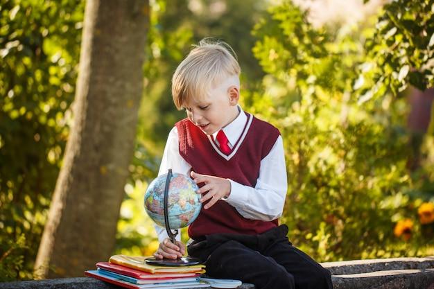 Entzückender schüler mit büchern und kugel an draußen. bildung für kinder. zurück zum schulkonzept. Premium Fotos