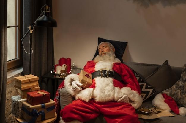 Entzückender weihnachtsmann, der ein schläfchen hält Kostenlose Fotos