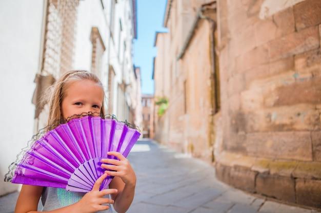 Entzückendes glückliches kleines mädchen, das draußen selfie in der europäischen stadt nimmt. porträt des kaukasischen kindes genießen sommerferien in der alten stadt Premium Fotos