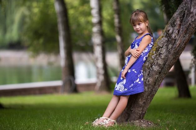 Entzückendes hübsches kleinkindmädchen mit dem langen blonden haar im modischen kleid, das auf baumstamm sich lehnt. Premium Fotos