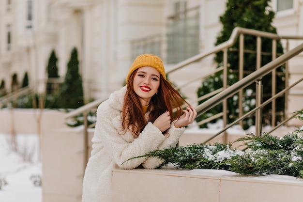 Entzückendes ingwermädchen im hut, das positive gefühle ausdrückt. wunderschönes weibliches modell, das sich im winter entspannt. Kostenlose Fotos