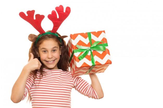 Entzückendes junges mädchen mit einem weihnachtsgeschenk Premium Fotos