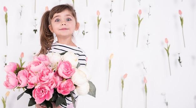 Entzückendes junges mädchen mit rosafarbenem blumenstrauß Kostenlose Fotos