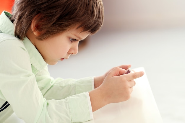 Entzückendes kind, das mit einem smartphone spielt Kostenlose Fotos