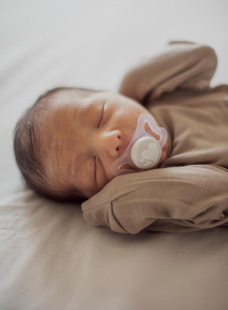 Entzückendes kleines baby mit friedensstifter Premium Fotos