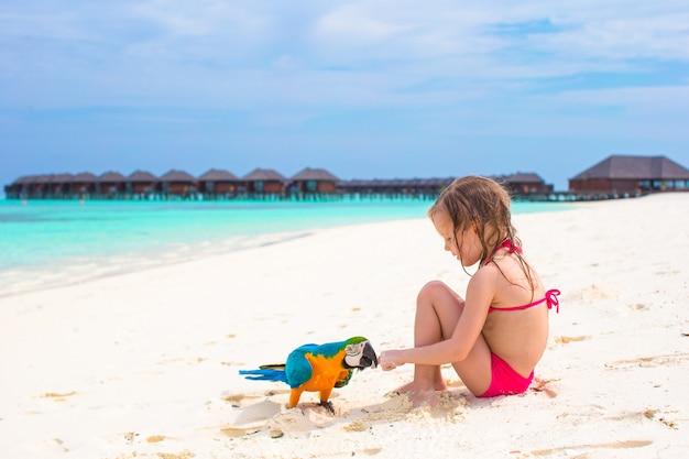 Entzückendes kleines mädchen am strand mit buntem papagei Premium Fotos