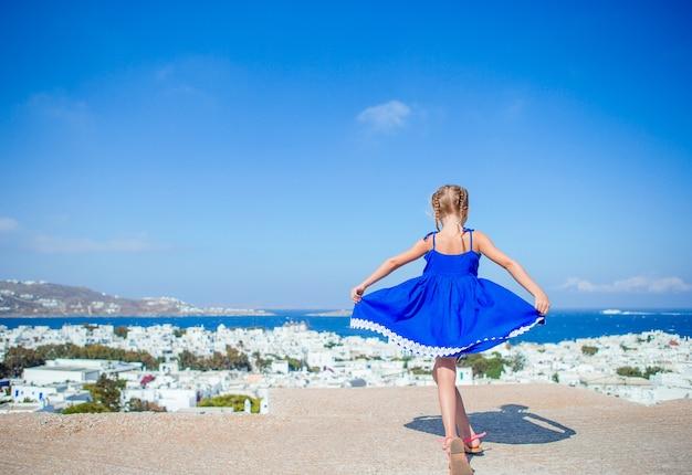 Entzückendes kleines mädchen an der alten straße des typischen griechischen traditionellen dorfs Premium Fotos