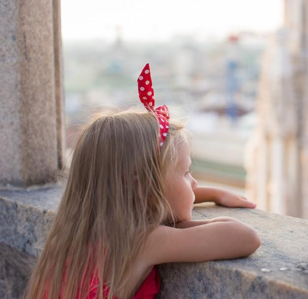 Entzückendes kleines mädchen auf der dachspitze des duomo, mailand, italien Premium Fotos