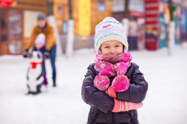 Entzückendes kleines mädchen auf eisbahn mit vater und schwester Premium Fotos