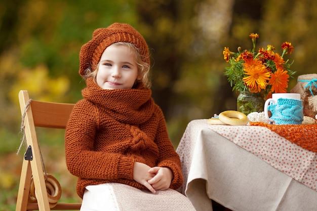 Entzückendes kleines mädchen auf picknick im herbstpark. Premium Fotos